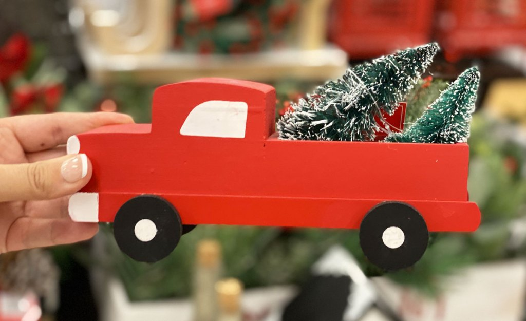 woman holding up a woden red truck with christmas tree in back