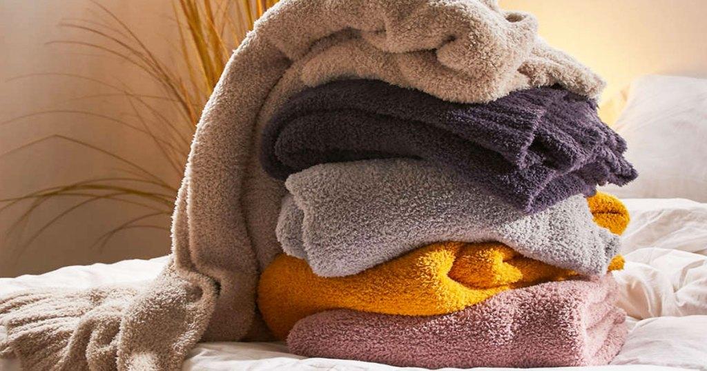 tumpukan selimut mewah terlipat di atas tempat tidur