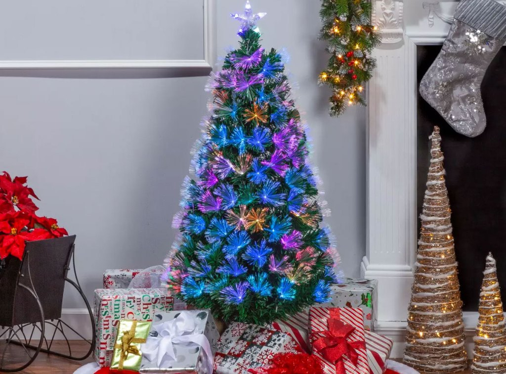 multi-color fiber optic christmas tree near fire place with wrapped presents at base