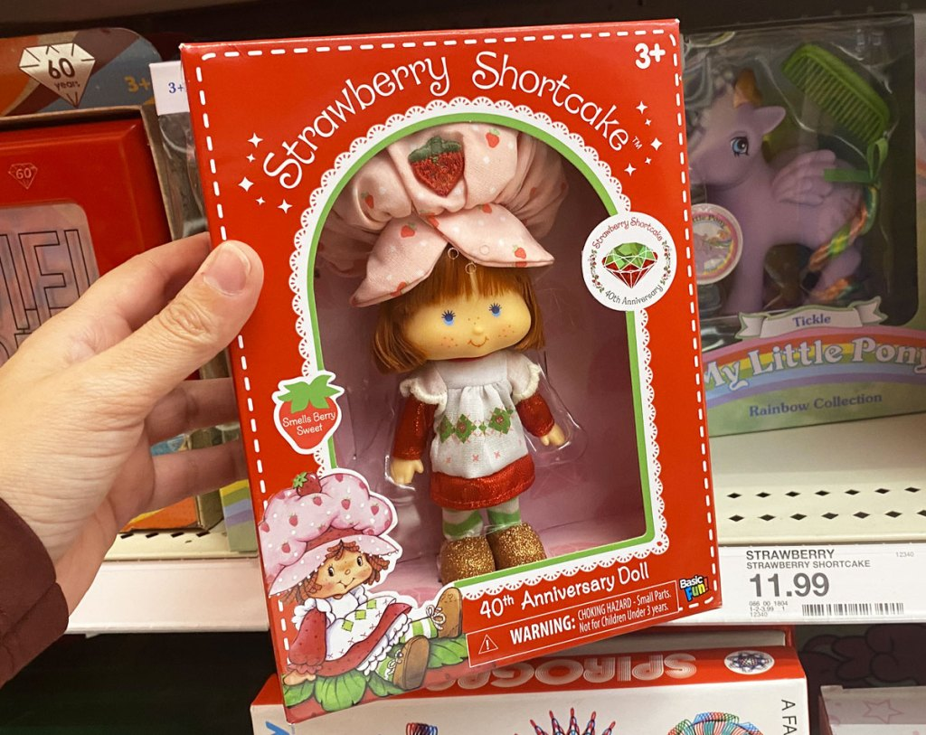 person holding up strawberry shortcake doll in a red box