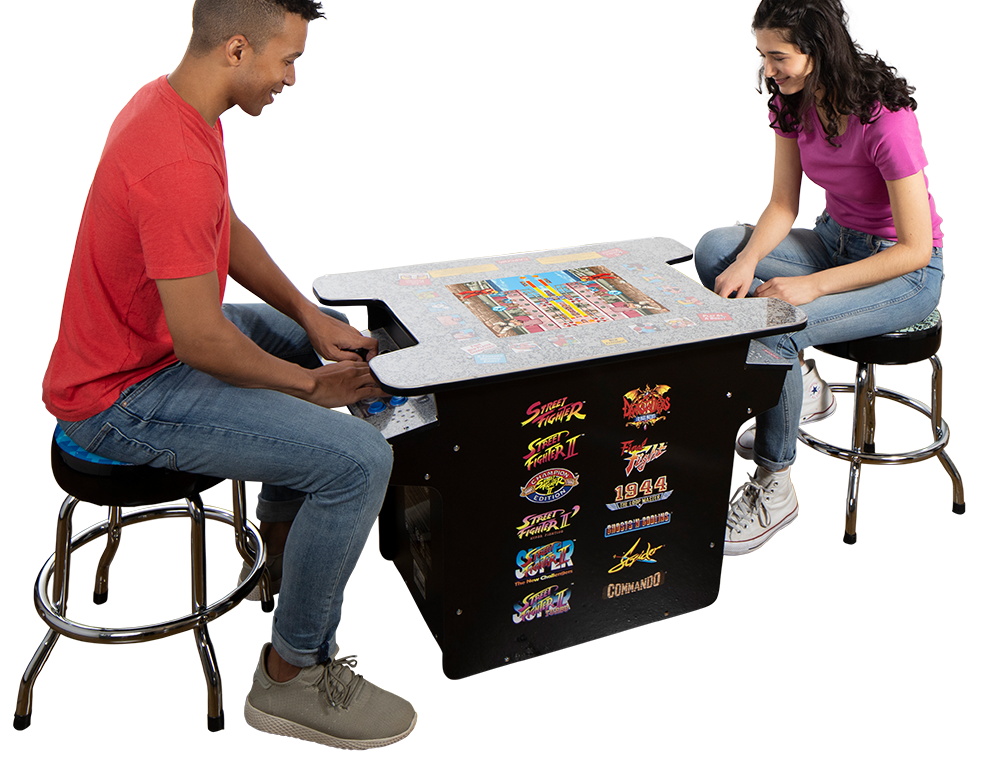 two people playing on a table arcade