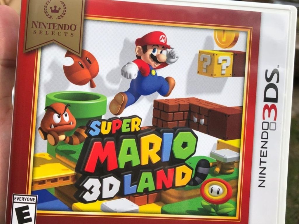hand holding Super Mario 3D Land game