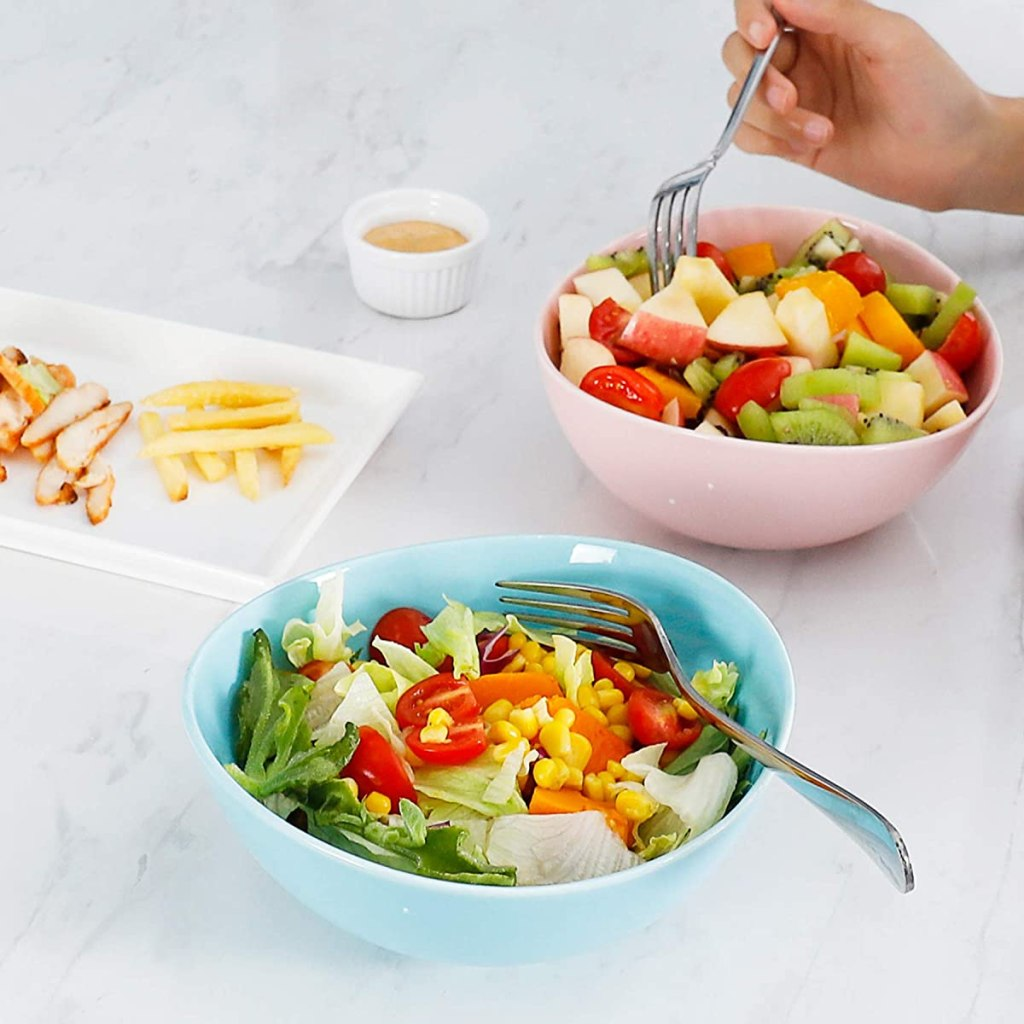 two bowls with salads in them