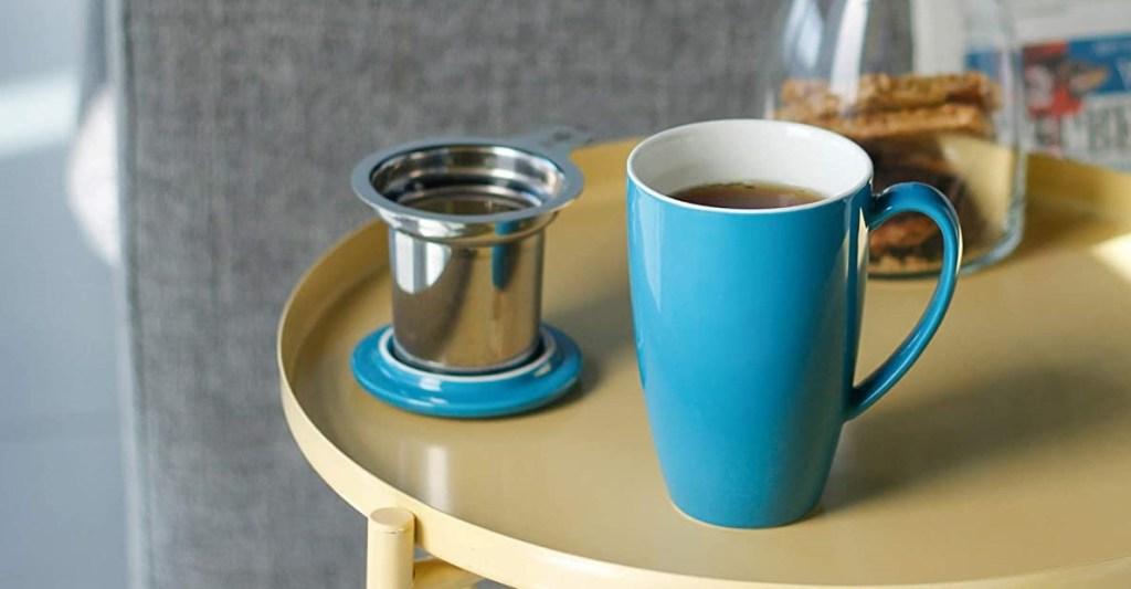 teal tea mug with infuser on a table