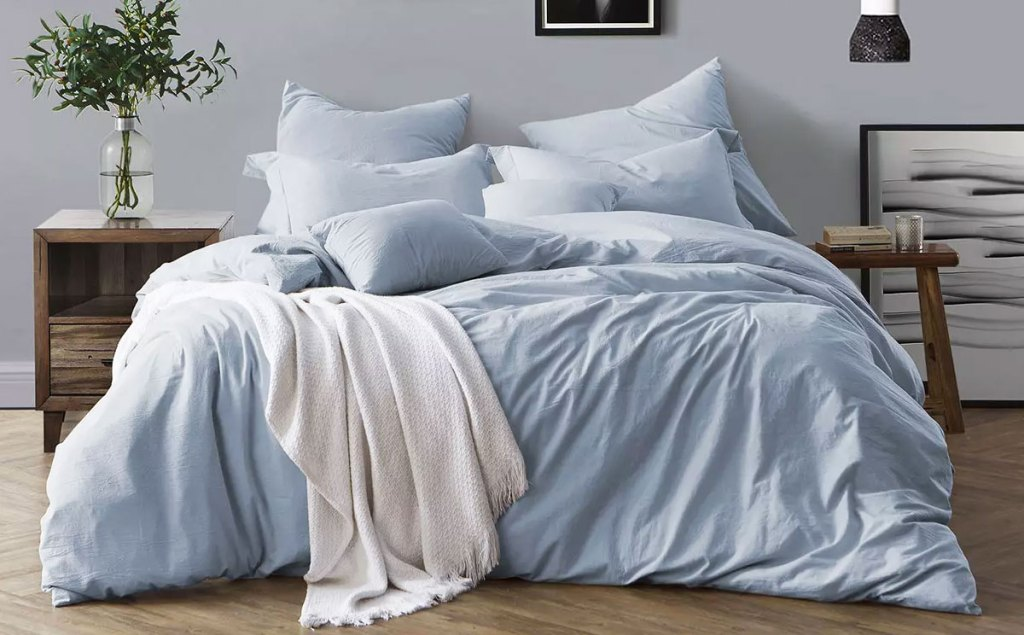 light blue colored duvet set on bed with matching pillow cases and a white throw blanket
