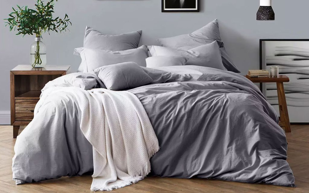 grey colored duvet set on bed with matching pillow cases and a white throw blanket