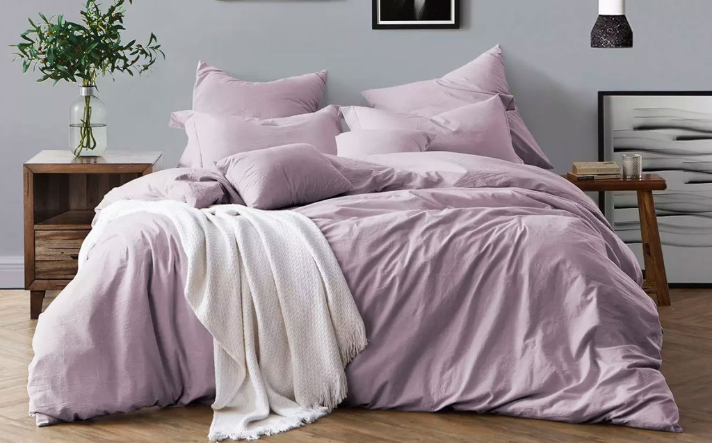 lavender colored duvet set on bed with matching pillow cases and a white throw blanket