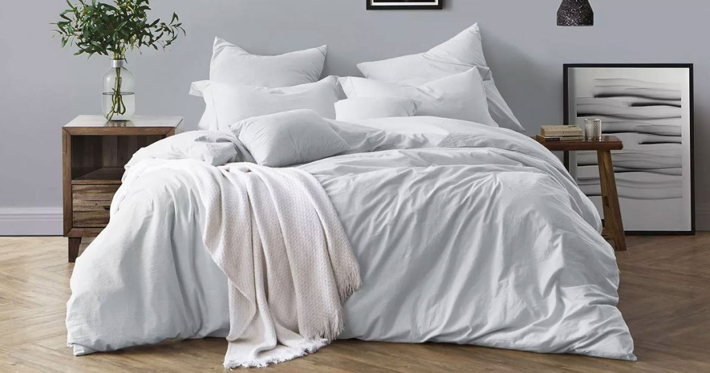 pale blue colored duvet set on bed with matching pillow cases and a white throw blanket