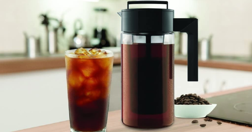 Takeya Patented Deluxe Cold Brew Coffee Maker filled with cold brew coffee next to a glass with coffee and ice cubes