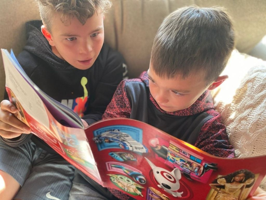 Two little boys looking through the Target 2020 Holiday Toy Book