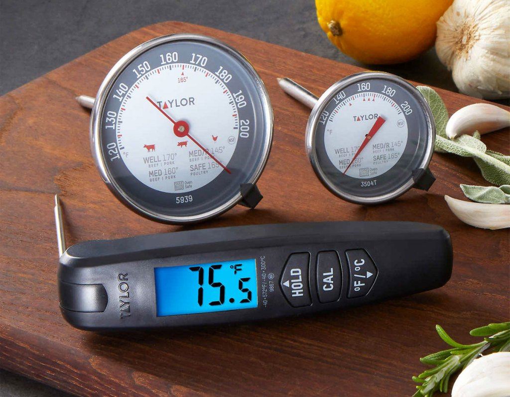 two round meat thermometers and a digital thermometer on a wood cutting board