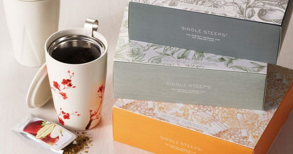 three tea forte gift sets next to a mug with tea in it