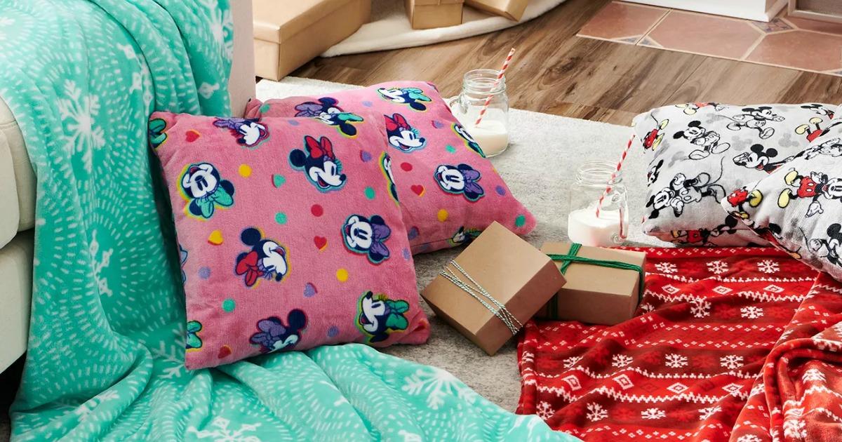 Minnie Mouse themed throw pillows on a floor near Mickey Mouse pillows