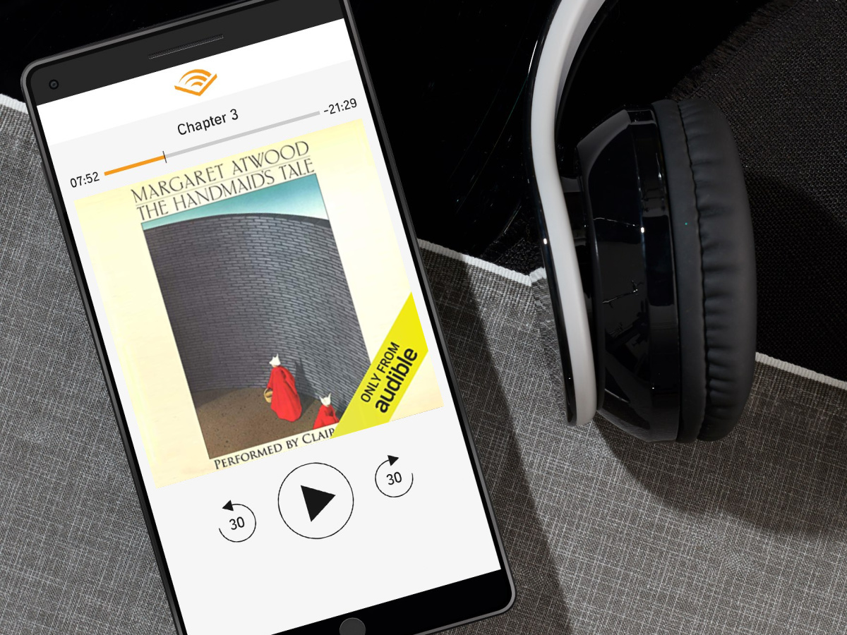 phone playing audiobook with headphones next to it