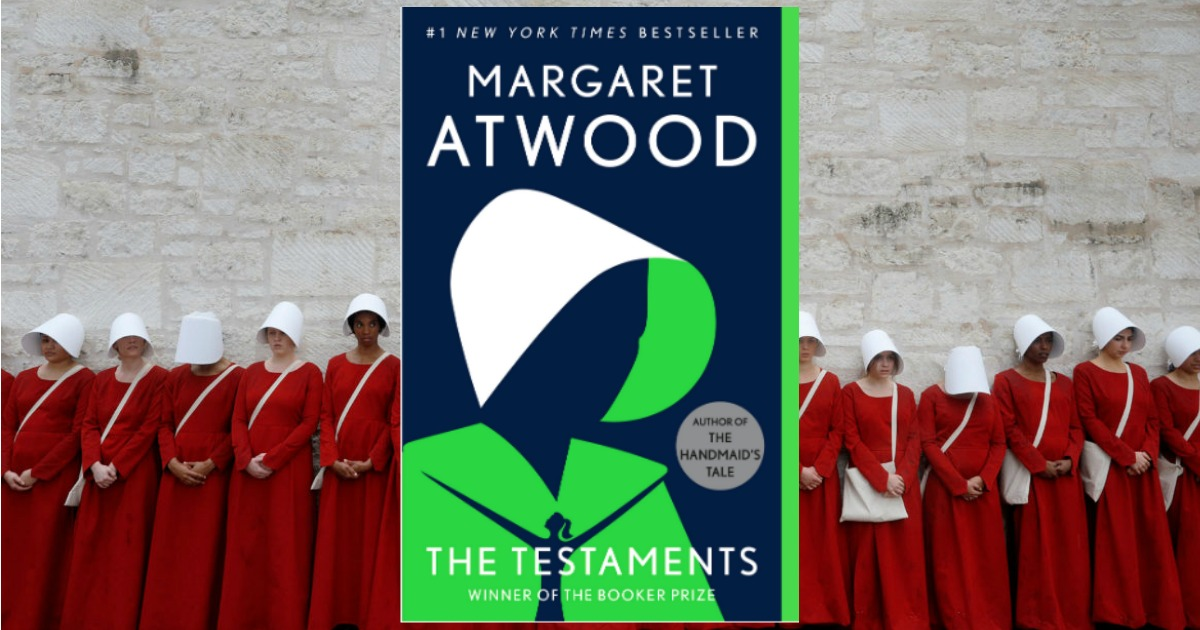 stock image of The Testaments by Margaret Atwood cover art over a picture of women in red dresses and white hats