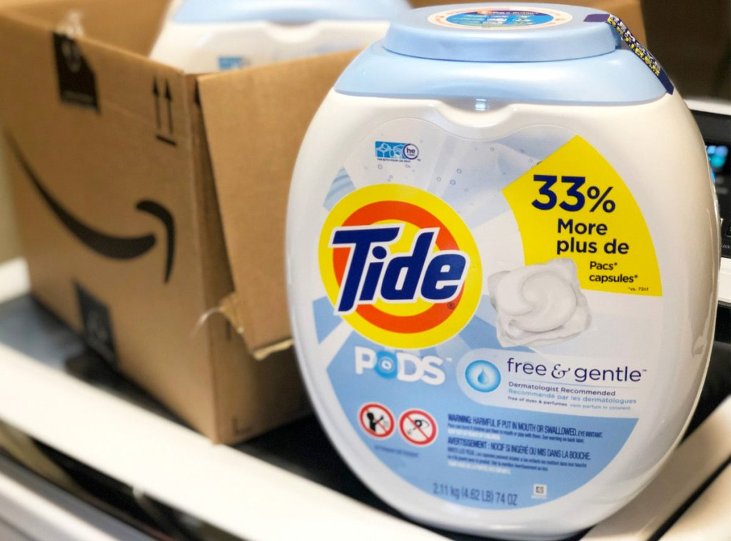 white container of tide free and gentle laundry detergent pods on washing machine near amazon box