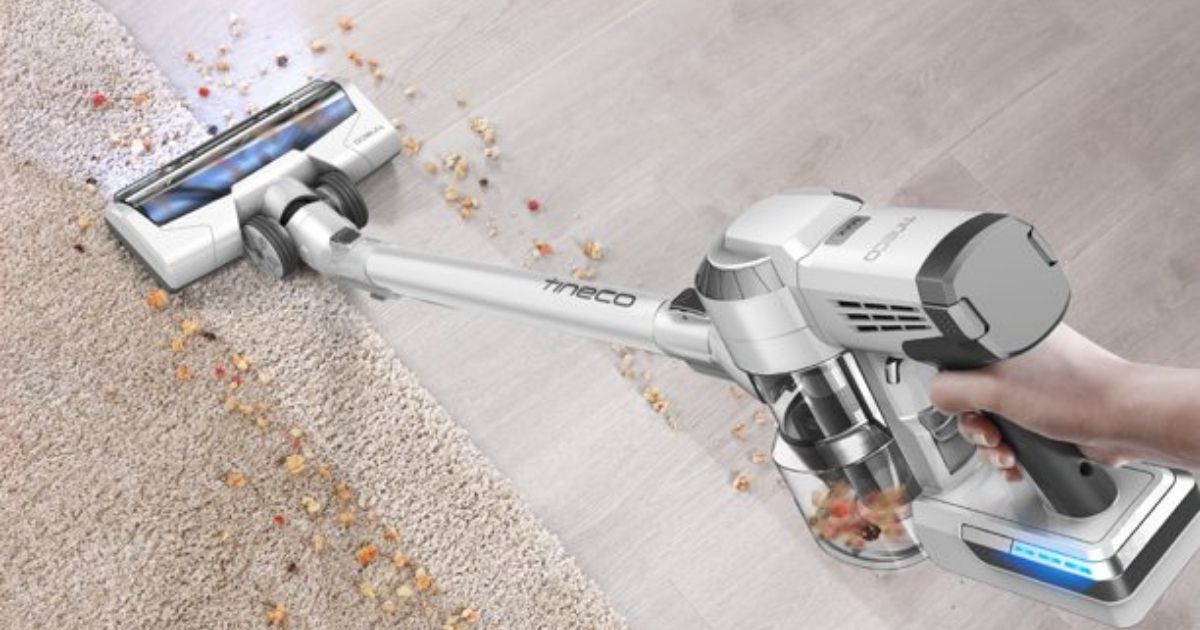 hand using a cordless vacuum to clean up debris on the carpet