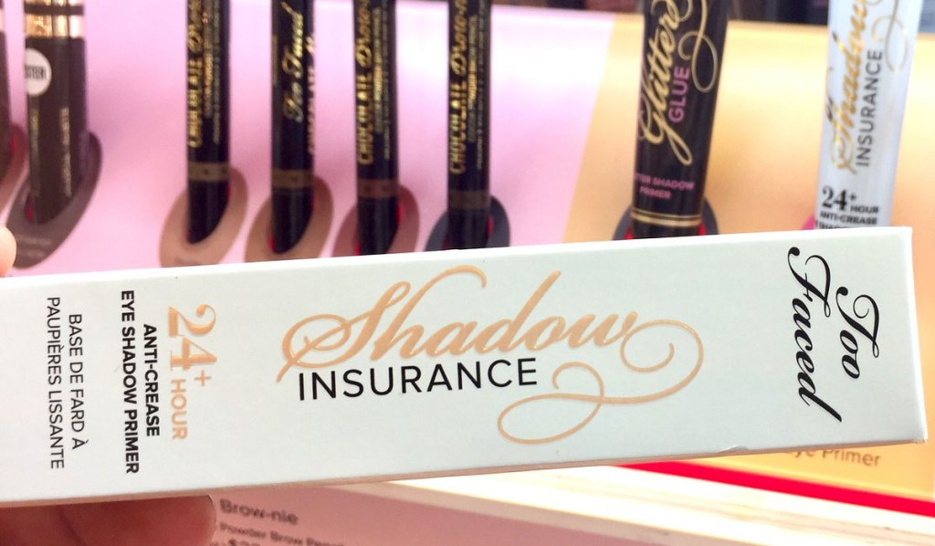 person holding up blue box of too faced shadow insurance primer