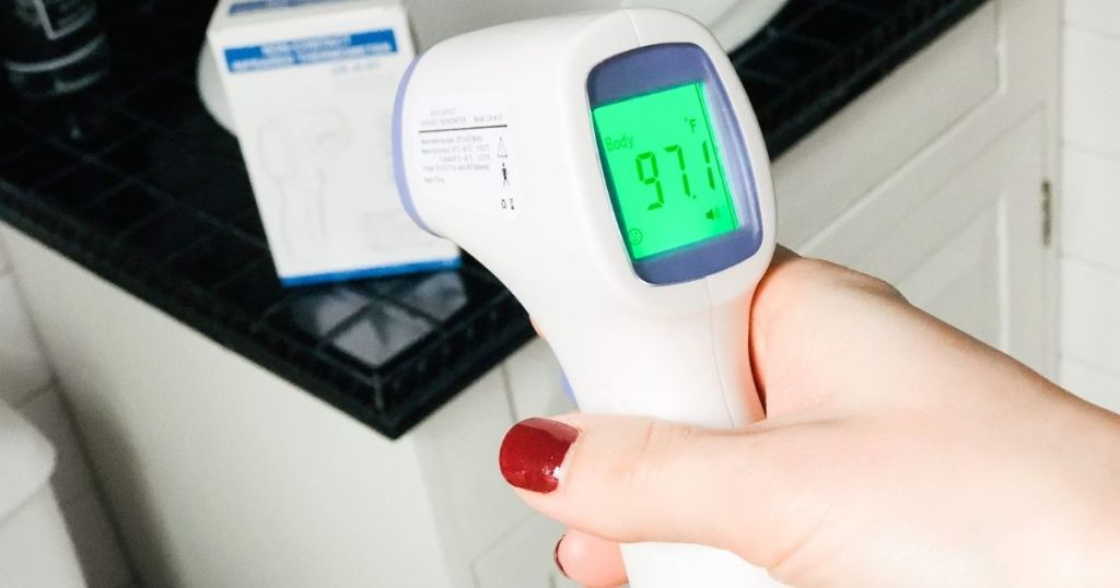 hand holding digital thermometer with screen reading 97.1
