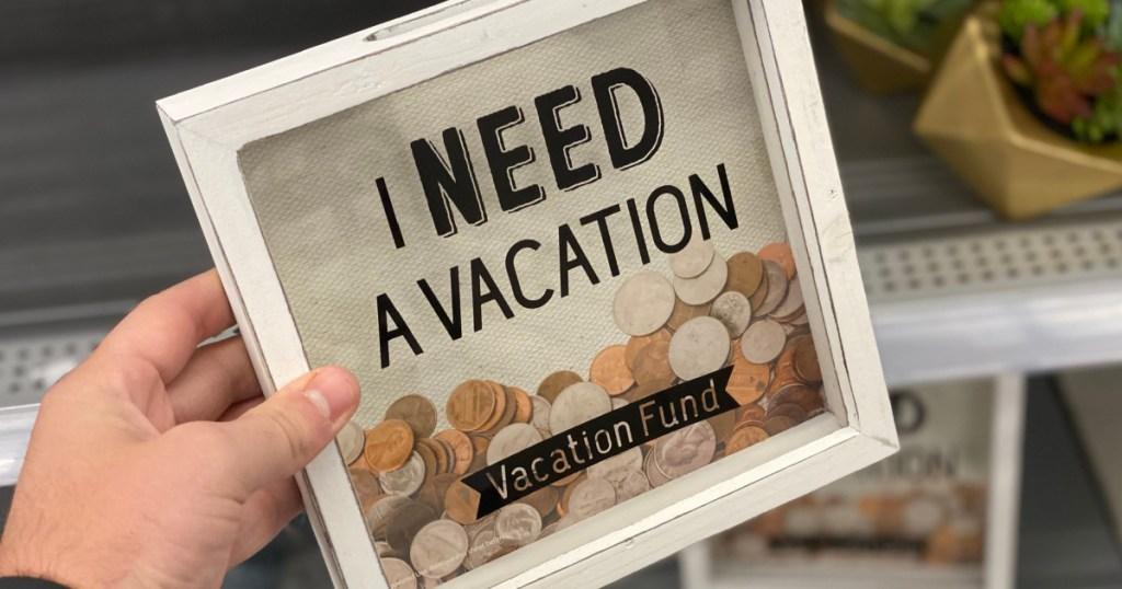 hand holding 'i need a vacation' bank at walmart