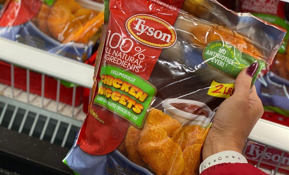 Sebuah tangan memegang sekantong chicken nugget Tyson di toko