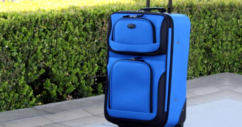 blue suitcase on sidewalk