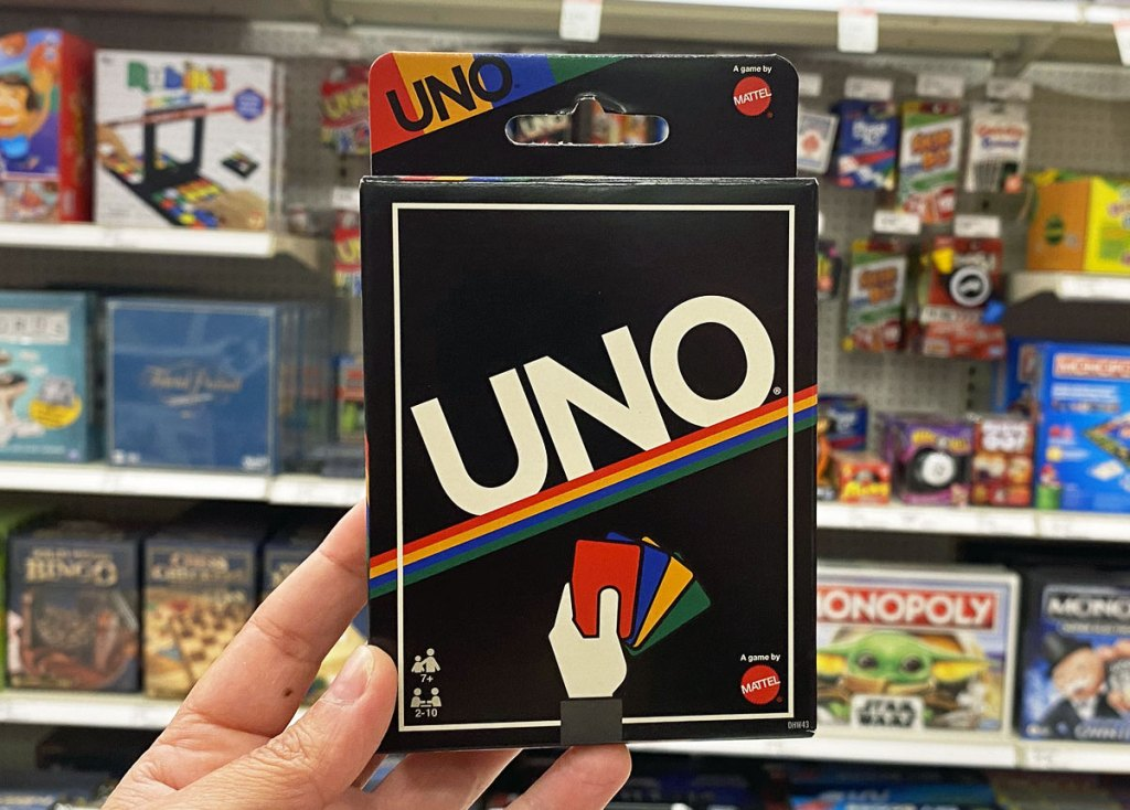 person holding up a retro themed UNO card game in toy aisle of target