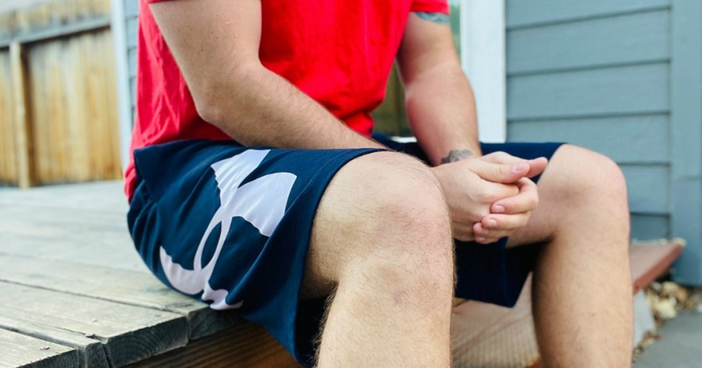 man sitting on a deck wearing under armour shorts