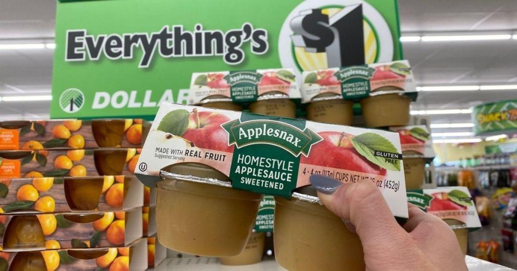 Sebuah tangan mengambil sebungkus saus apel dari rak toko