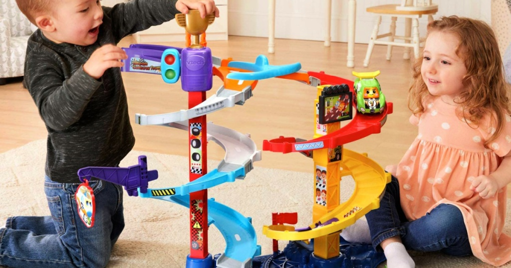 kids playing with a VTech Go! Go! Smart Wheels Ultimate Corkscrew Tower