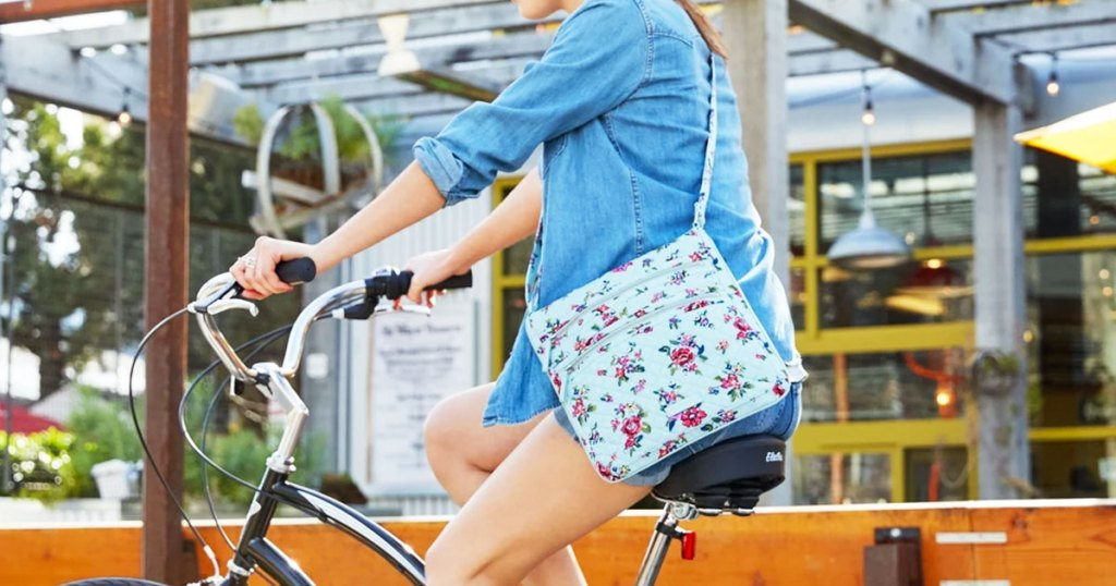 woman riding on bike wearing denim shirt and light blue with floral print crossbody bag