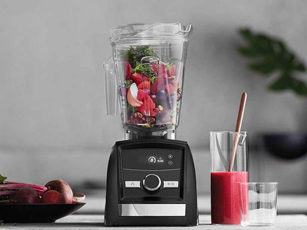 Vitamix blender with fruits and veggies in container