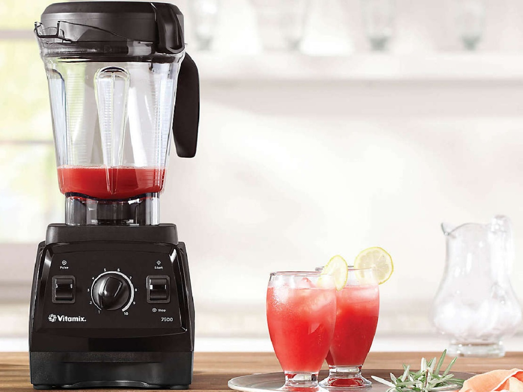 black blender on counter with cups of red drink