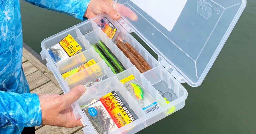 person holding a clear fishing tackle box filled with fishing accessories