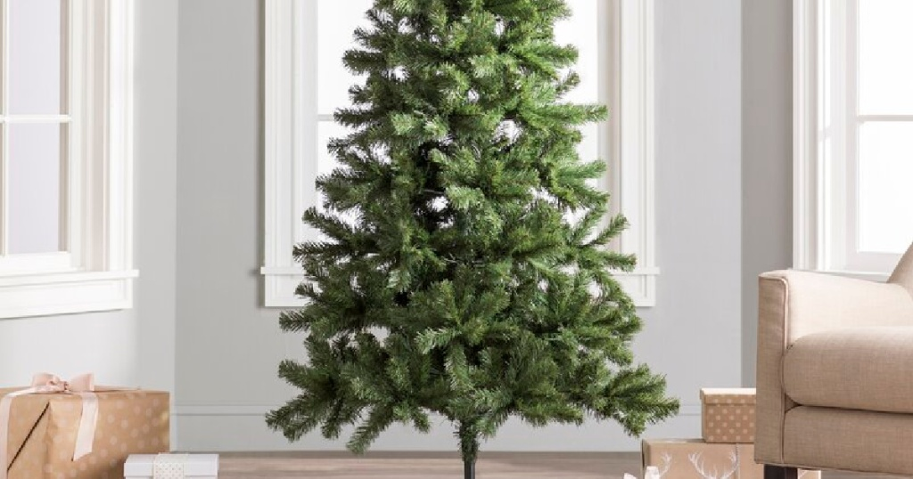 Christmas Tree in the middle of a living room next to a chair and presents