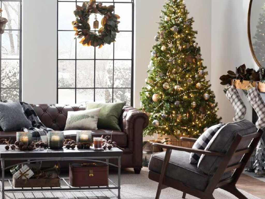 fully decorated christmas tree in a living room next to a window and holiday decor