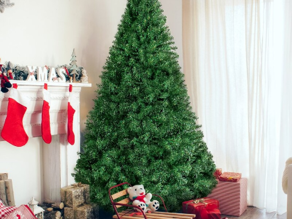 large green christmas tree next to a fireplace mantle and stockings with presents underneath