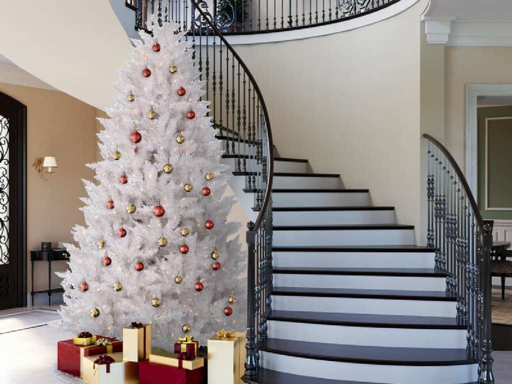 white artificial christmas tree with red ornaments next to a stairwell and presents underneath