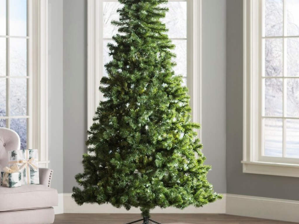 christmas tree next to a chair in a living room in front of windows