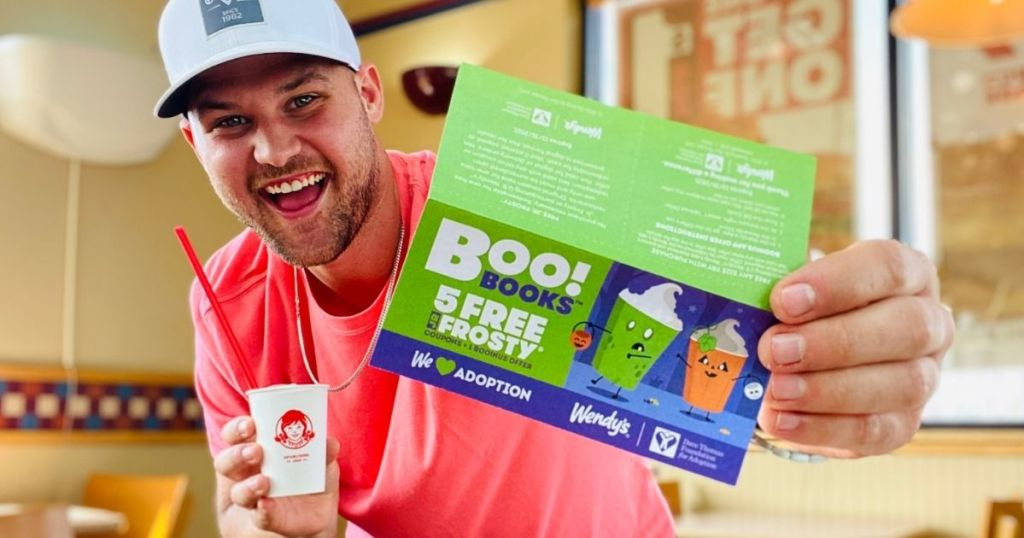 man holding a frosty and a Wendy's boo book
