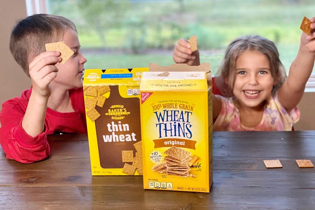 Dua anak sedang makan biskuit di sebuah meja