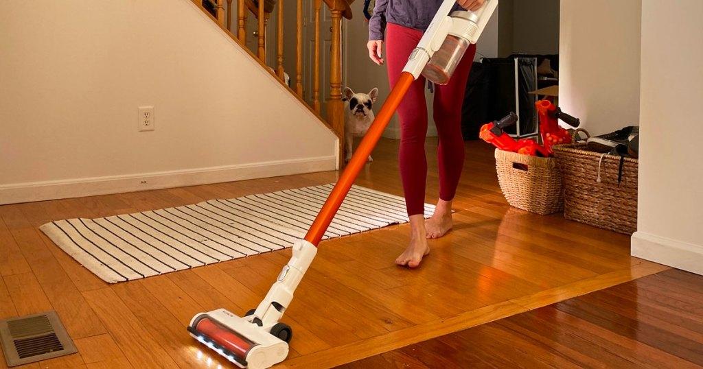 woman in red leggings using cordless stick vacuum to clean hardwood floors