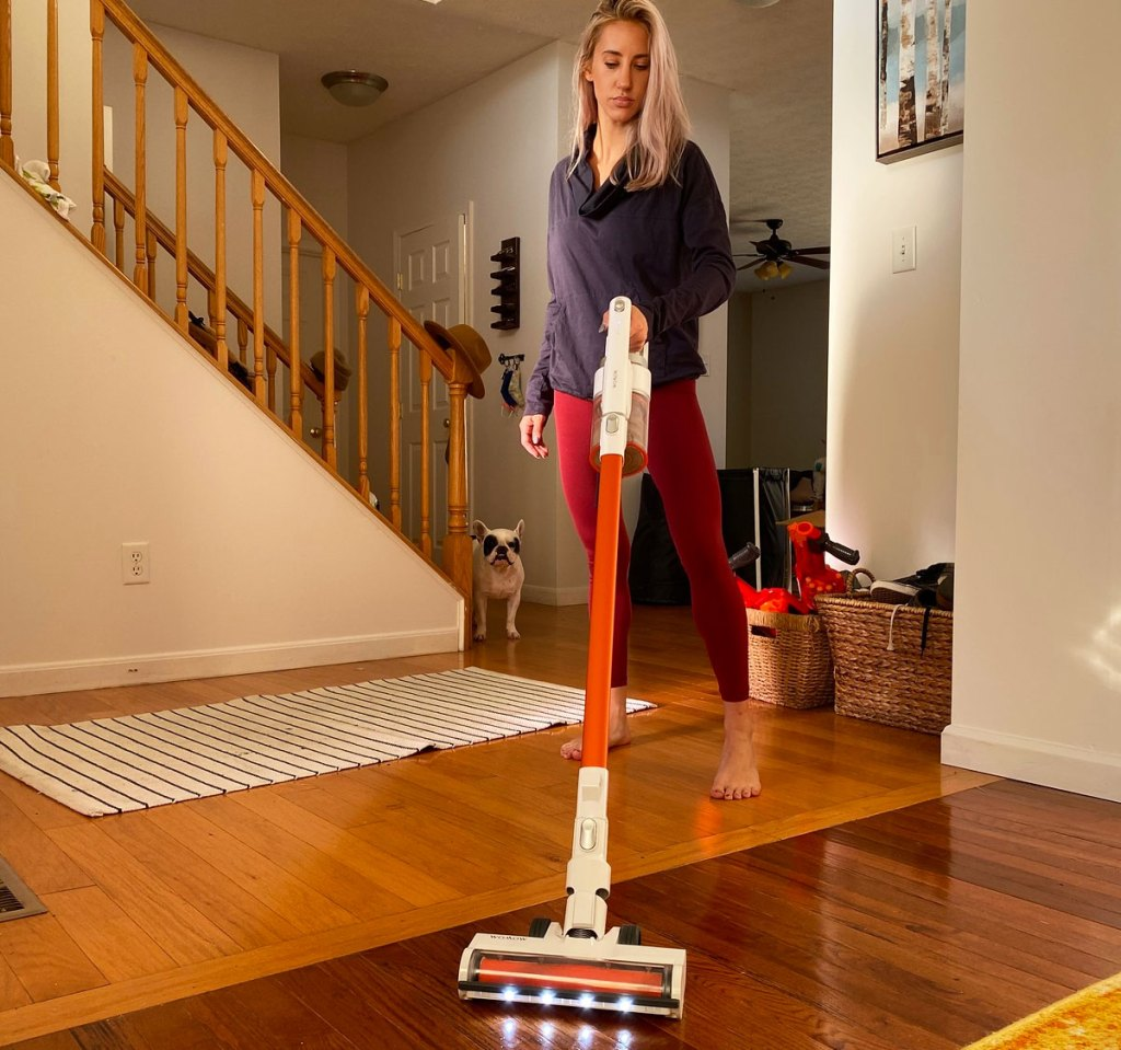 blonde woman in workout apparel using cordless stick vacuum to clean hardwood floors