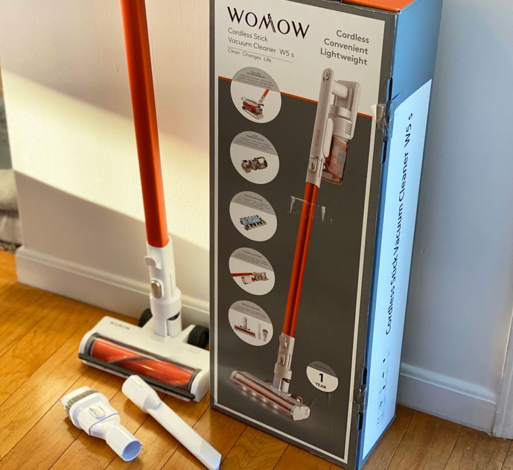cordless stick vacuum cleaner with two attachments next to it's box