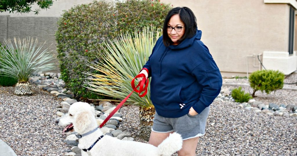 woman outside wearing navy blue hoodie and walking white dog