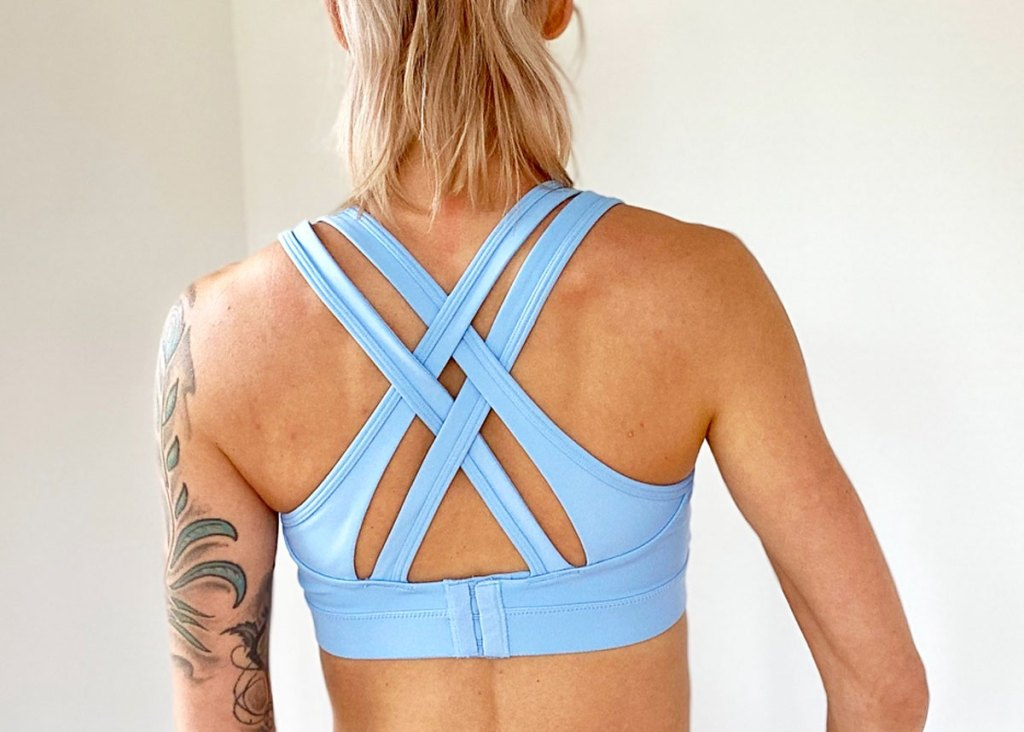 woman with blonde hair wearing a light blue sports bra with crossing back straps
