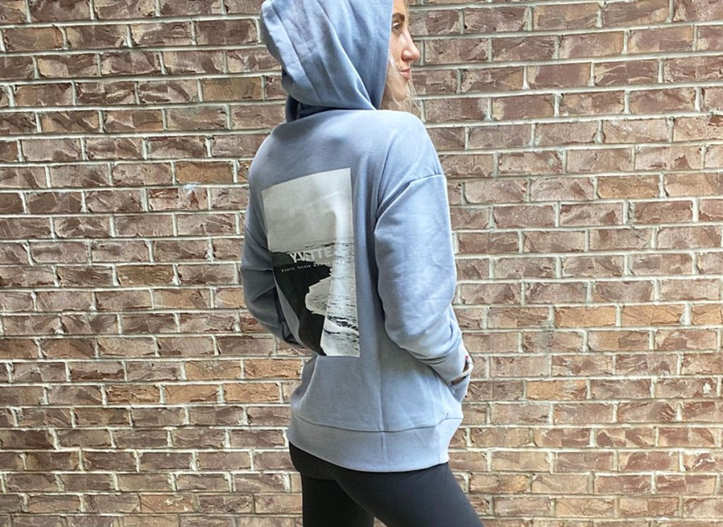 woman standing in front of brick wall wearing a light blue hoodie with beach scene printed on back