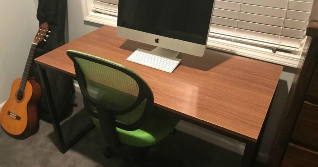 Large wooden desk near green desk chair