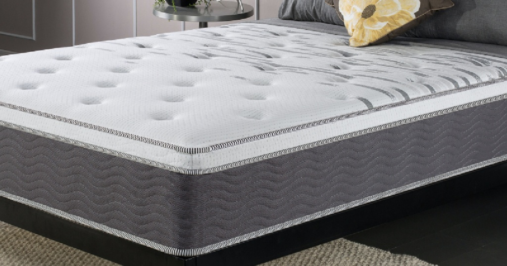 Zinus queen size mattress on a bed frame with pillows
