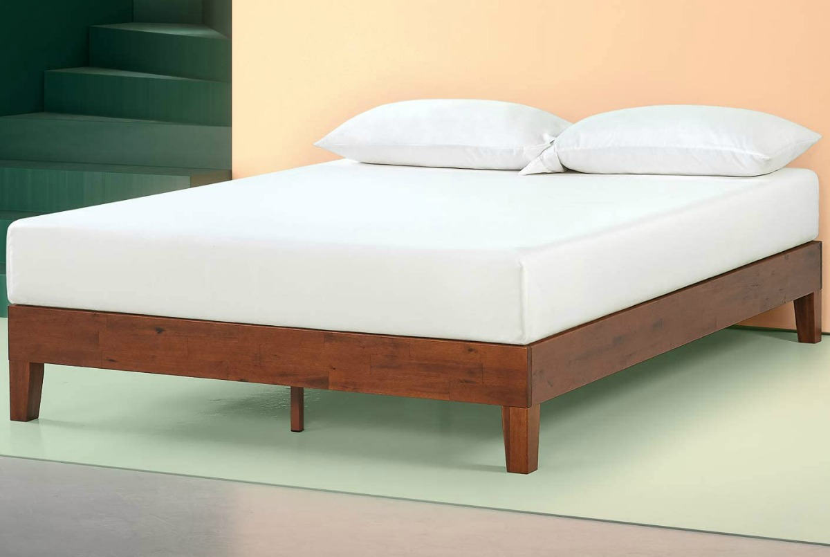 Large wooden queen sized bed with a white mattress and white pillows